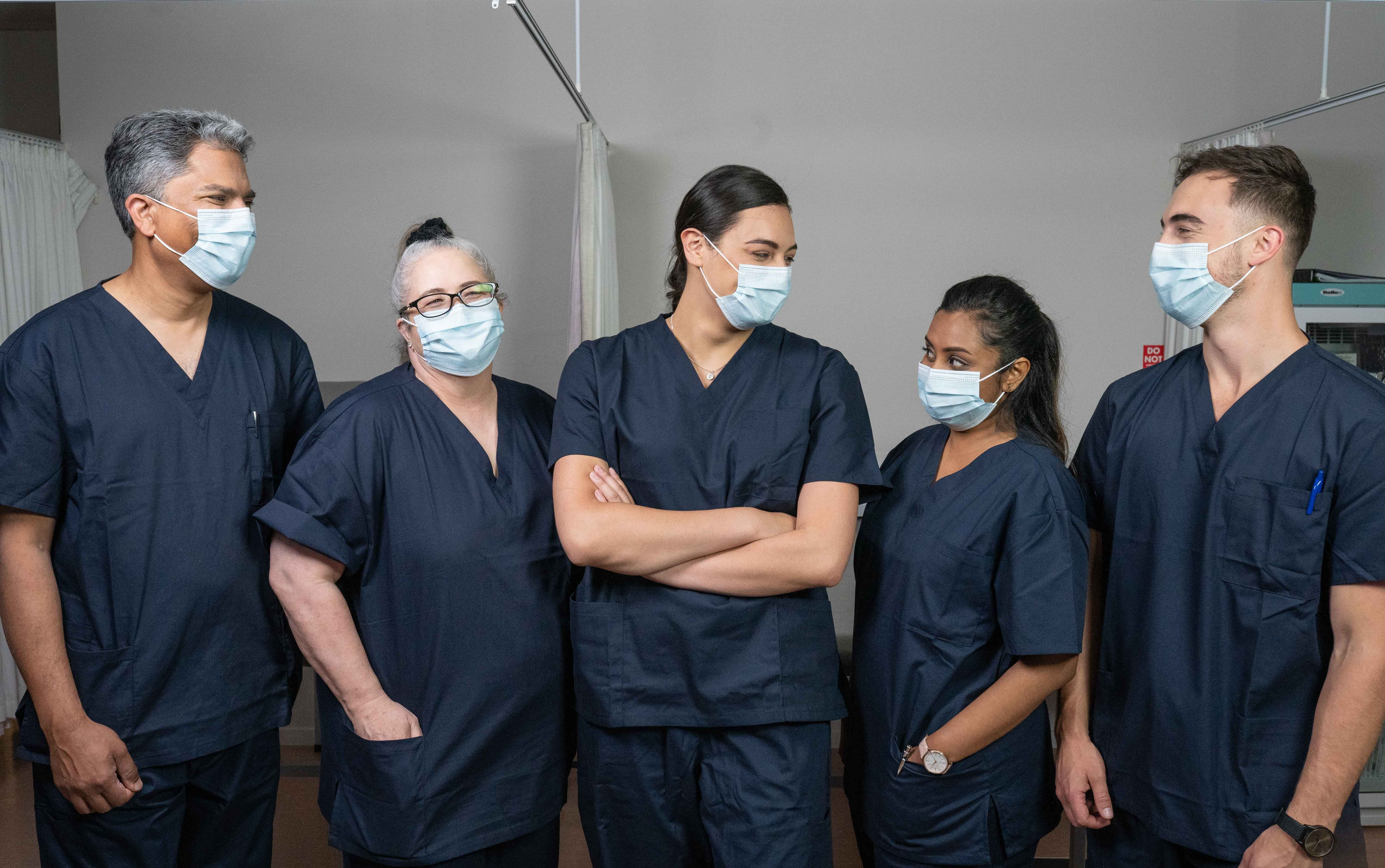 Five doctors in scrubs and masks